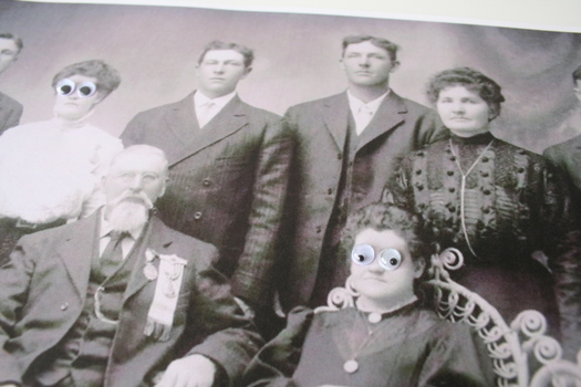 vintage group photo of ancestors with googly eyes glued to it